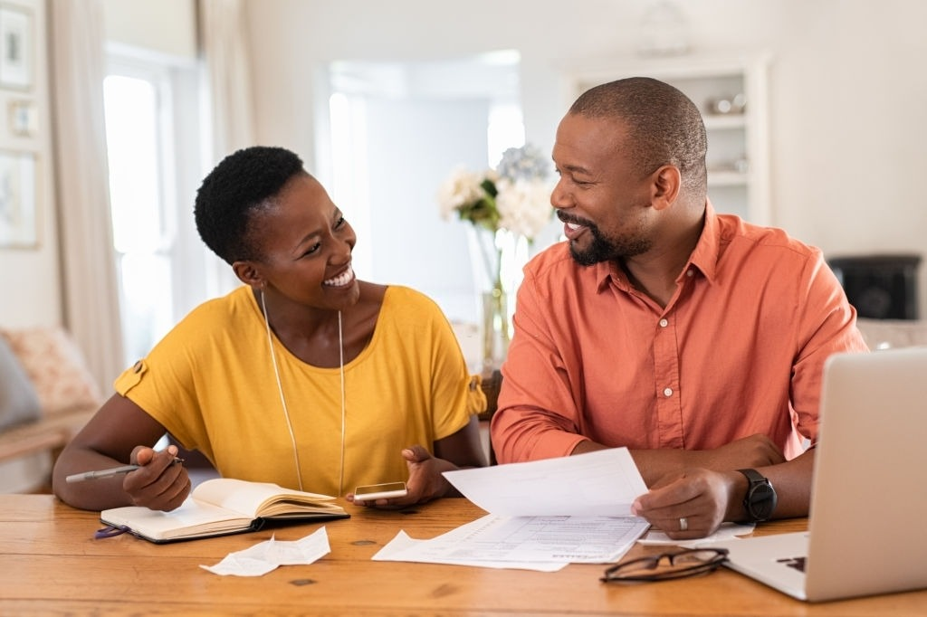 Cheerful mature couple sitting and managing expenses at home. Happy african man and woman paying bills together and managing budget. Black smiling couple checking accountancy and bills while looking at each other.